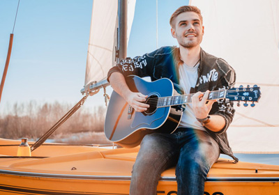 Maximilian Jäger mit Gitarre auf einem Segelboot